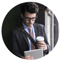 Business man holding coffee looking at tablet.
