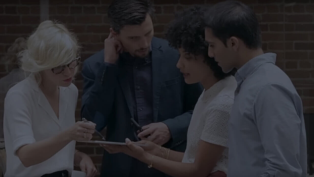 Group of professionals looking over tablet