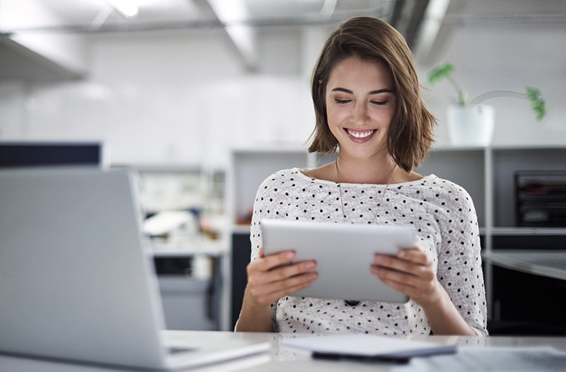 Smiling businesswoman on tablet device in bright office