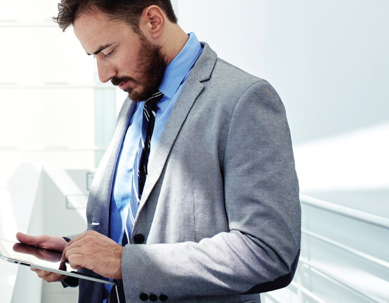 Business executive using tablet computer away from desk