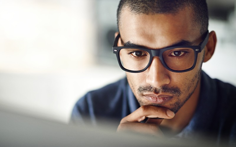 Male with glasses working on desktop device